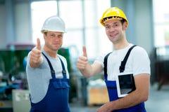Arbetare två i fabrik med tummen upp Royaltyfri Foto