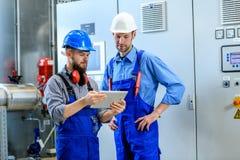 Arbetare två i industrianläggning arkivbilder