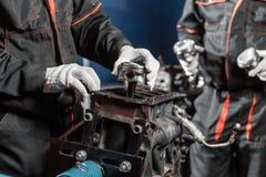 Arbetare två, mekanikern installerar en ny pistong Demonter medlet för motorkvarteret Motorisk huvudreparation Sexton ventiler Royaltyfri Fotografi