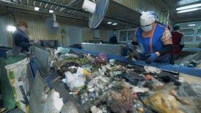 Arbetare väljer upp avskräde från transportör, slut lager videofilmer