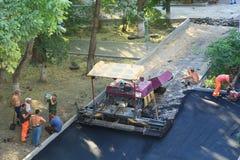 Arbetare vilar nära asfaltpaveren i aftonen Royaltyfri Bild