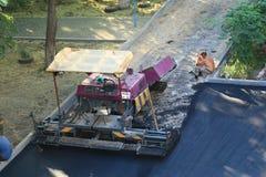 Arbetare vilar nära asfaltpaveren i aftonen Arkivfoton