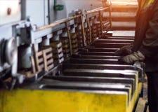 Arbetaren är förlovad i klipp av metall på produktionautomathjälpmedlet, metallklipp, närbilden, press arkivbilder