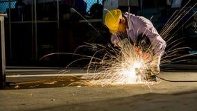Arbetaren använder att mala klippt metall, fokus på prålig ljus linje av shaen royaltyfria foton