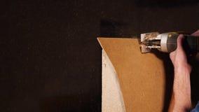 Arbetaren använder den elektriska sågen på en kryssfaner lager videofilmer