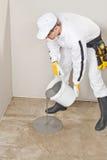 Arbetaren applicerar det självutjämnande golvet fotografering för bildbyråer