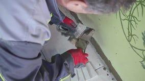 Arbetaren applicerar lim för en tegelplatta på en vägg stedicam som shoting stock video