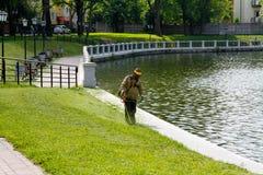Arbetaren av en trädgård klipper av ett gräs nära dammet i Kalinigrad Royaltyfri Foto