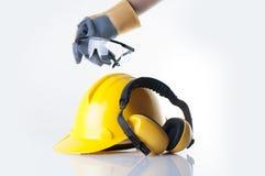 Arbetaren bär den läderhandsken och hackan upp säkerhetsexponeringsglaset på vit bakgrund royaltyfri fotografi