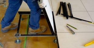 Arbetaren bär ett sväva golv på stålfot Arkivfoto