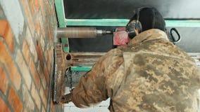 Arbetaren borrar en vägg med kraftiga makthjälpmedel lager videofilmer