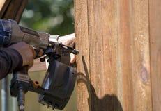 Arbetaren bygger det nya staketet med spikar vapnet arkivfoton