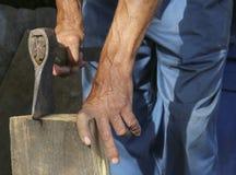Arbetaren, en man med en yxa som hugger av vedträ anställd Royaltyfri Foto
