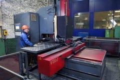 Arbetaren följer arbetet av maskinen för att borra stålplattor Arkivfoto