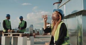Arbetaren för den unga kvinnan från konstruktionsplats i varm arbetsdag har lite avbrottsdricksvatten, bakgrundsbyggmästare har stock video