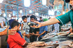 Arbetaren för fiskmarknaden räcker ut den mobila betalningterminalen till partnern Arkivbild