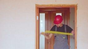 Arbetaren fixar, eller reparationer inredörren tar bort mätningar, med en skruvmejsel och en linjal stock video