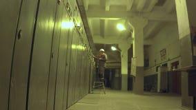 Arbetaren går till elektriskt rum och skriver data lager videofilmer