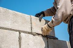 arbetaren gör betongväggen vid cement att blockera och rappa på construen royaltyfria bilder