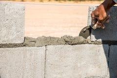 arbetaren gör betongväggen vid cement att blockera och rappa på construen royaltyfri fotografi