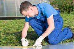 Arbetaren gör mätningar av en plast- genomskinlig räkning för växthuset, närbild arkivbilder