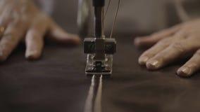 Arbetaren gör sömmar på lädermaterial vid symaskinen i fabrik close upp arkivfilmer