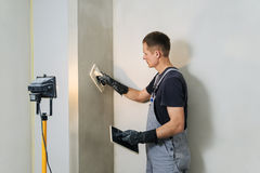 Arbetaren gör sista släta murbruk på väggen Arkivfoton