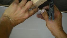 Arbetaren gör taket av MDF-paneler arkivfilmer