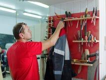 Arbetaren hänger hans omslag i hans funktionsdugliga rum Royaltyfria Foton
