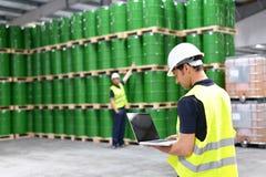 Arbetaren i ett lager med olje- trummor kontrollerar materielet arkivbilder