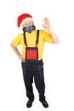 Arbetaren i gasmask och den santa hatten säger högt. Royaltyfri Foto