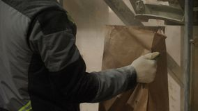 Arbetaren i maskering tar den pappers- påsen med den torra byggande blandningen lager videofilmer