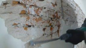 Arbetaren i skyddande dräkt demolerar murbrukväggen E stock video