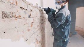Arbetaren i skyddande dräkt demolerar murbrukväggen E personligt skyddande för utrustning r stock video