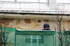 Arbetaren i skyddande exponeringsglas och en respirator bearbetar väggen med en vinkelmolar, innan återställande och han rappar Royaltyfri Bild