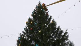 Arbetaren i vaggan av manipulatoren dekorerar julgranen arkivfilmer