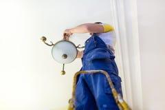 Arbetaren i workwear installerar en ljuskrona och förbinder den till elektricitet på taket från stege i lägenhet I fotografering för bildbyråer