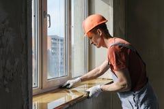 Arbetaren installerar en fönsterfönsterbräda Arkivfoto