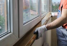 Arbetaren installerar en fönsterfönsterbräda royaltyfri bild
