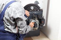 Arbetaren installerar en olje- gasbrännare Arkivfoto