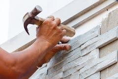 Arbetaren installerar yttersida för stenväggen med cement för hus Arkivfoto