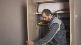 Arbetaren justerar dörrarna i kabinettet och installerar maskinvaran, tillbehör stock video
