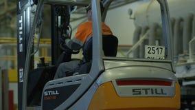 Arbetaren kör gaffeltrucken till träpaletter