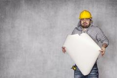 Arbetaren kan inte klara av med planen av byggnader Arkivbild
