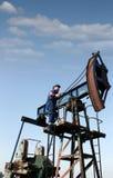 Arbetaren klättrar upp till pumpstålar Royaltyfri Fotografi
