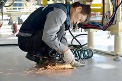 Arbetaren klipper av en metalldetalj med hjälp av ett handcirkulär s Fotografering för Bildbyråer