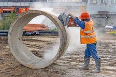 Arbetaren klipper den konkreta cirkeln arkivbild