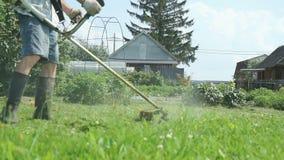Arbetaren klipper gräset med en gräsklippare utomhus arkivfilmer