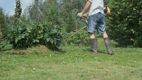 Arbetaren klipper gräset med en gräsklippare utomhus lager videofilmer