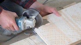Arbetaren klipper keramiska tegelplattor med en vinkelmolar Mycket damm stock video